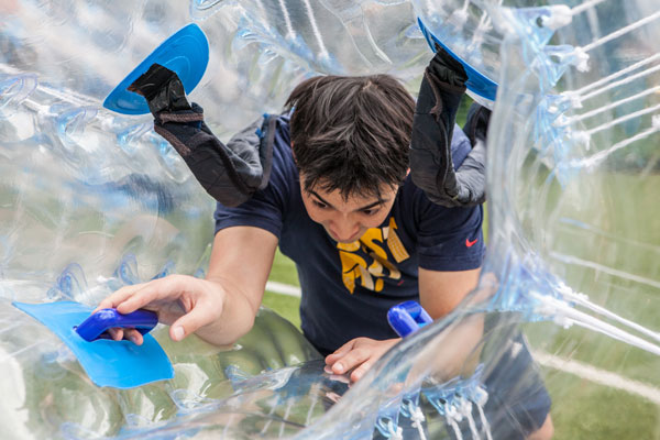 Player climbing inside a bubble to play bubble football