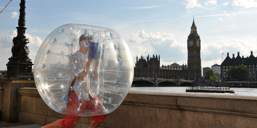 Man running inside a bubble football bubble along the Thames in front of Big Ben in Westminster